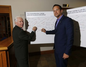 Minister Varadkar and Gay Byrne sign the pledge not to use a mobile phone while driving.